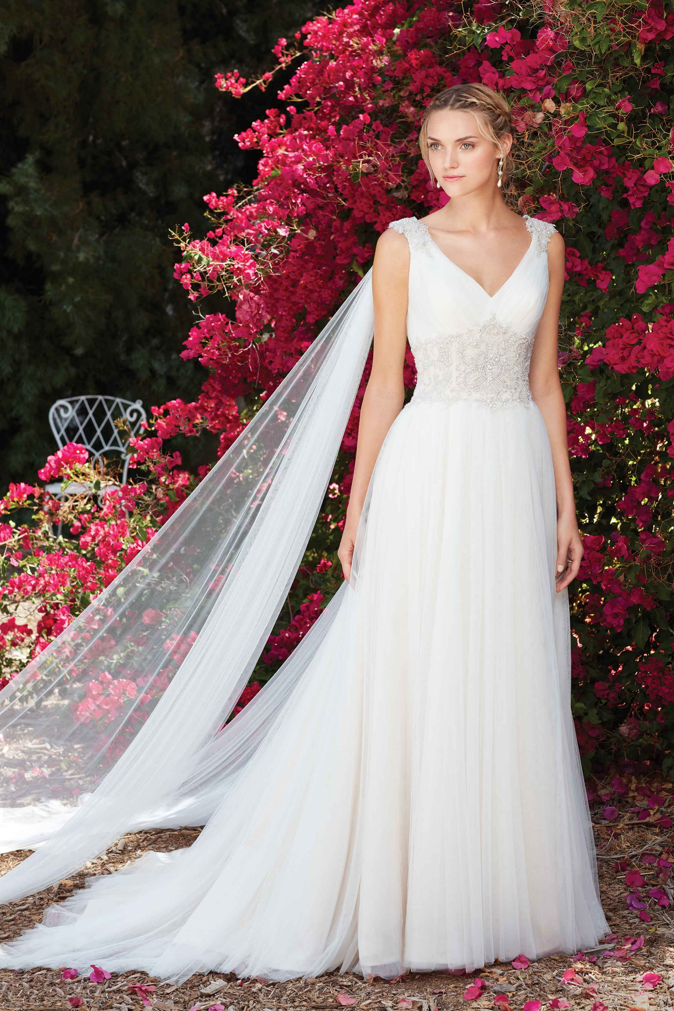 a79f543bd The plunging V-shape neckline ends at a sparkling cluster of beading that  wraps ...